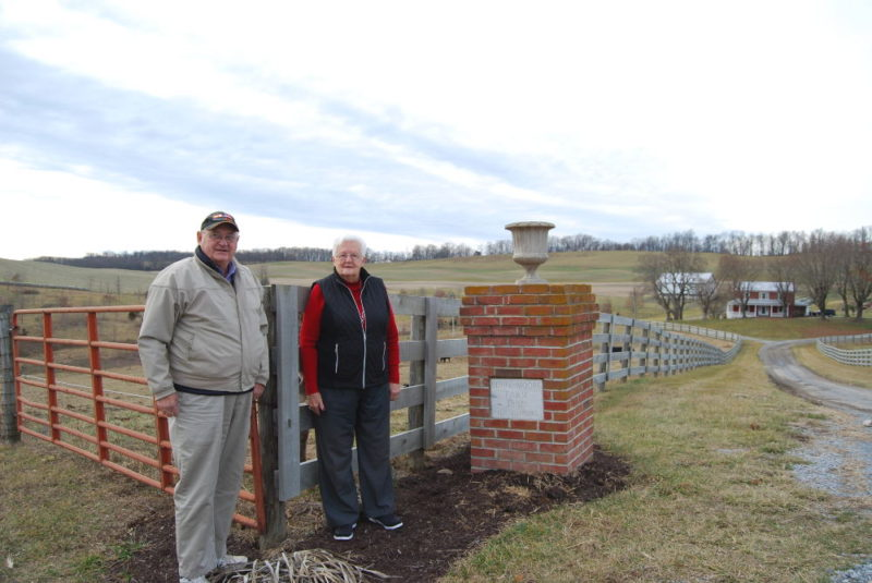 Don and Sue Hanger by the entrance gate to Berry-Moore Farm